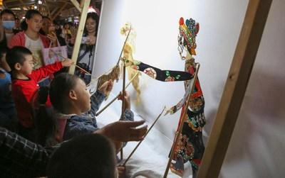 Niños disfrutan teatro de sombras en la feria del patrimonio cultural intangible de North Street, Xiangyang, Provincia de Hubei. (PRNewsfoto/Xiangyang Municipality)