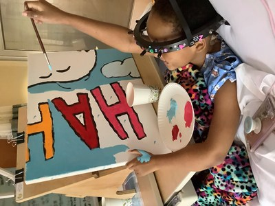 "Flying High with Woodstock: Young patient Za'Nii Roundtree shows off her awesome painting skills as she contributes to a new Snoopy and Woodstock mural at Gillette Children's in St. Paul, Minnesota—hometown of Peanuts creator Charles Schulz. The mural is one of 70 being donated to hospitals worldwide by Peanuts Worldwide and the nonprofit Foundation for Hospital Art as part of the global ""Take Care With Peanuts"" initiative, launched October 2in conjunction with the 70th Anniversary of Peanuts"