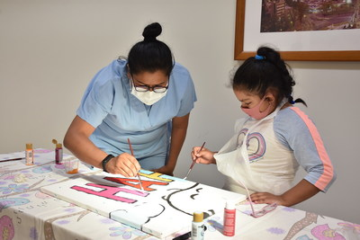 "Brushing Up on Happiness with Snoopy: At Hospital Shriners Para Ninos in Mexico City, Guadalupe Lino and young patient Silvia paint the Snoopy and Woodstock mural donated to the hospital by Peanuts Worldwide and the nonprofit Foundation for Hospital Art. The mural is one of 70 donated to hospitals worldwide as part of the global ""Take Care With Peanuts"" initiative, launched October 2 in conjunction with the 70th Anniversary of Peanuts."